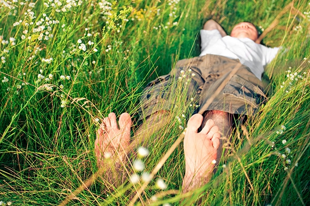 Mann liegt schlafend im Gras