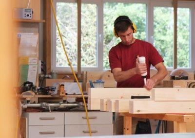 Schreiner verleimt Teile eines Zirbenbettes in der Schreinerei Bauereiß