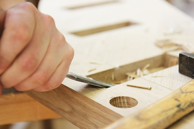 Schreiner der Schreinerei Bauereiß stemmt etwas aus einem Eicheholz