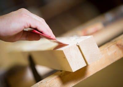 Schreiner trägt Leim auf Massivholz auf, um dieses zu verleimen