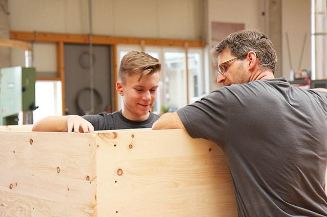 Zwei Schreiner der Schreinerei Bauereiß bauen einen Zirbenholz Kleiderschrank