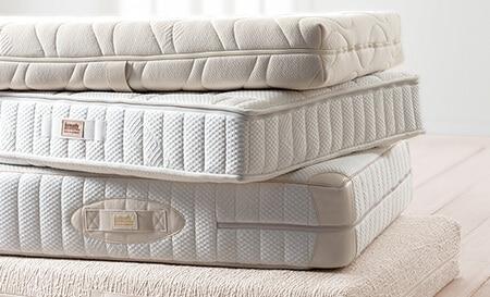Futonmatratze, Deluxe Matratze, Classic Matratze und Natural Matratze von dormiente auf einem Stapel