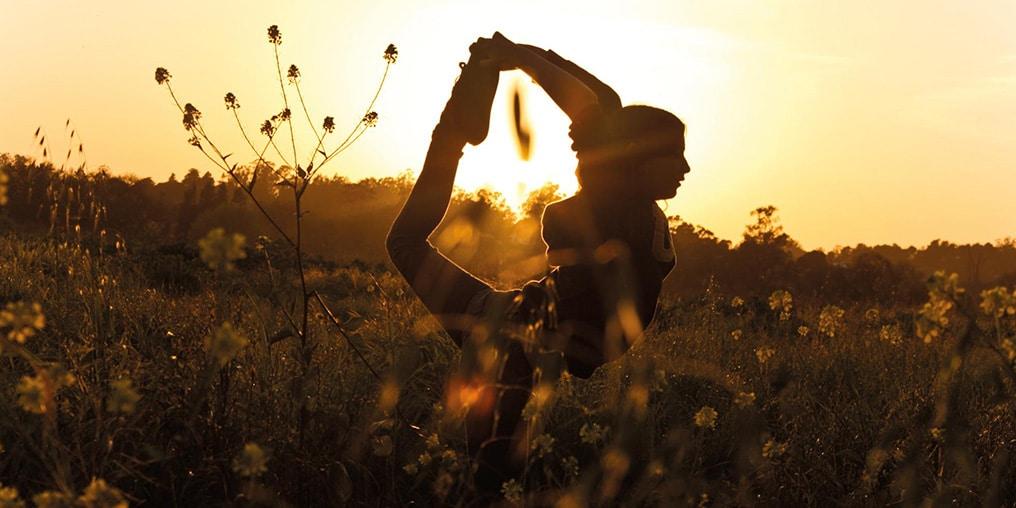 Frau macht bei Sonnenuntergang auf der Wiese eine Yoga-Übung