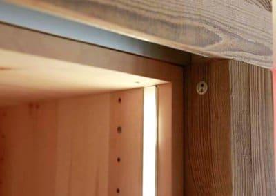 LED-Beleuchtung in einem Schrank aus Zirbenholz mit Schiebetüren