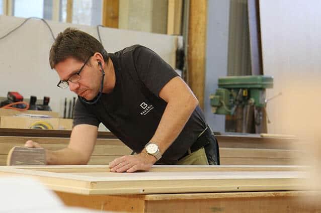 Schreiner schleift Holz