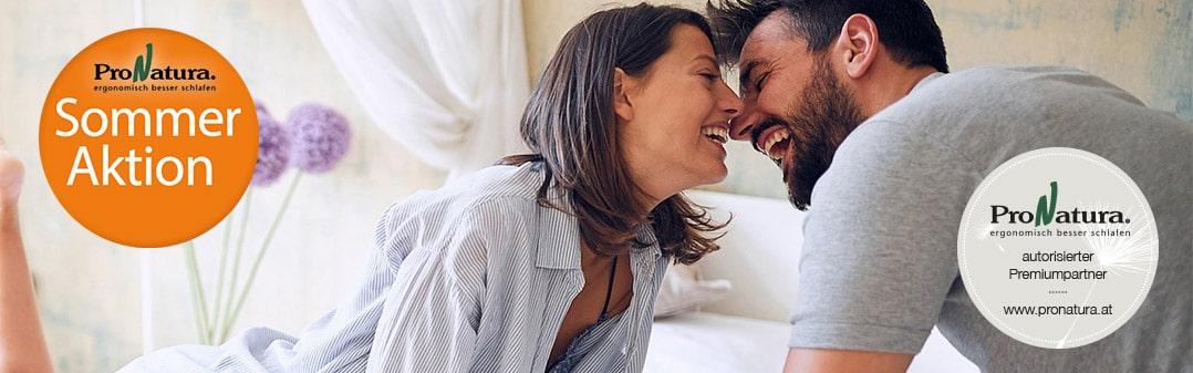 Mann und Frau Küssen sich auf Bio Sommerbettwäsche mit Störer von ProNatura Sommerliebe Aktion für Sommerbettwäsche