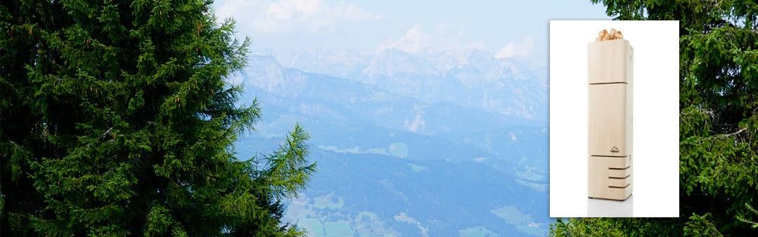 Zirbenraumlüfter von Allpine und im Hintergrund Zirbenkieferbäume und ein Gebirge in Salzburg